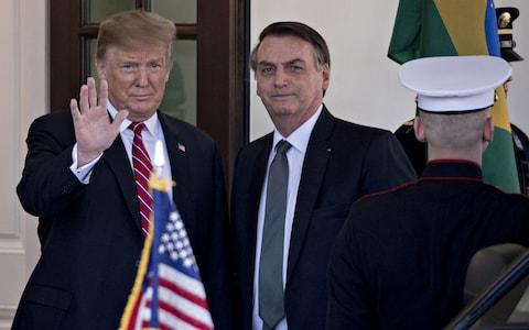 U.S. President Donald Trump, left, waves while standing with Jair Bolsonaro, Brazil's president, at the West Wing of the White House in Washington, D.C., U.S., on Tuesday, March 19, 2019. - Credit: Andrew Harrer/Bloomberg