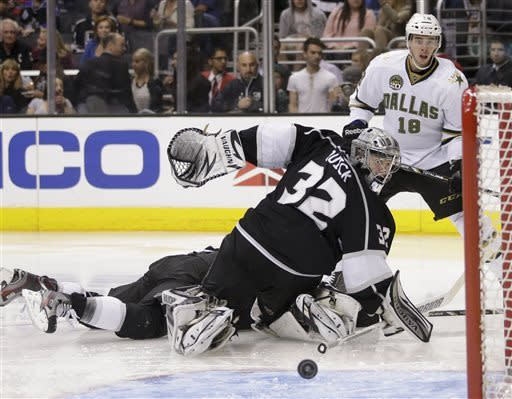 Los Angeles Kings goalie Jonathan Quick(32) and Dallas Stars' Reilly Smith(18) look at the puck during the third period of an NHL hockey game in Los Angeles, Sunday, April 21, 2013. The Kings won 4-3 in overtime. (AP Photo/Jae C. Hong)