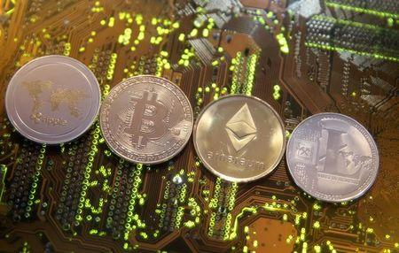FILE PHOTO: FILE PHOTO: Representations of the Ripple, Bitcoin, Etherum and Litecoin virtual currencies are seen on motherboard in this illustration picture