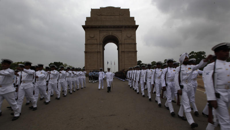 Soldiers from the three defense forces pay tribute at India Gate war memorial on the 13th anniversary of India's victory in the Kargil War in New Delhi, India, Thursday, July 26, 2012. Thursday marks the second day of the two-day celebrations of the 13th anniversary of its victory in the Kargil conflict, the 1999 conflict with Pakistan that raged for three months across the disputed Kashmir region had nearly brought the nuclear neighbors to a war. (AP Photo/Manish Swarup)