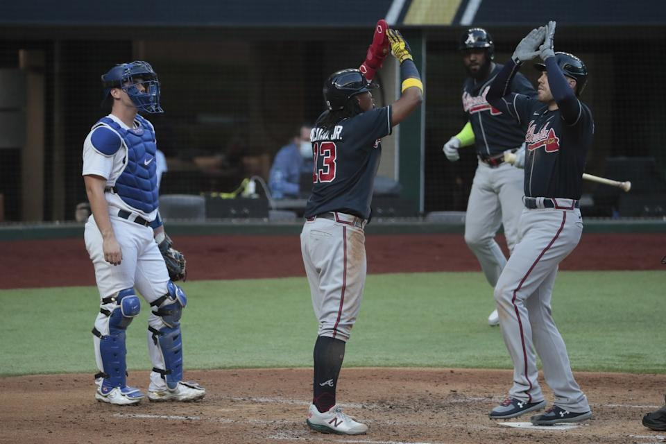 Atlanta's Freddie Freeman, right, celebrates with Ronald Acuna Jr. in front of Dodgers catcher Will Smith.