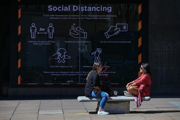 Social-distancing measures displayed in a shop window on Oxford Street in London, England.