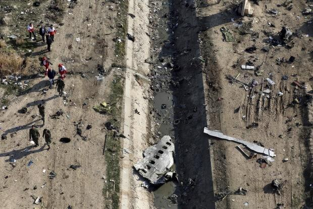 In this Wednesday, Jan. 8, 2020 photo, rescue workers search the area where a Ukrainian plane crashed in Shahedshahr, southwest of the capital Tehran, Iran. Iran's final report into the cause of the incident concludes an Iranian military unit