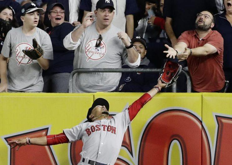 Red Sox right fielder Mookie Betts battles a fan for Chris Carter's fly ball. (AP)