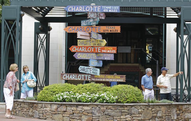 "This July 17, 2012 photo shows visitors walking past ""Charlotte"" signs at The Green park in downtown Charlotte, N.C. The Green, a 1.5-acre downtown park at 435 S. Tryon St., is a literary-themed park with sculptures of giant books, pages and a walkway of sounds. Bright signs mark the intersections of author names, including ""Emily"" and ""Bronte,"" ""Herman"" and ""Melville,"" and ""Alice"" and ""Walker."" (AP Photo/Chuck Burton)"