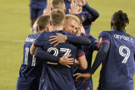 Chicago Fire defender Francisco Calvo (5) hugs forward Robert Beric (27) in celebration of Beric's goal against the New England Revolution during the first half of an MLS soccer match in Chicago, Saturday, April 17, 2021. (AP Photo/Mark Black)