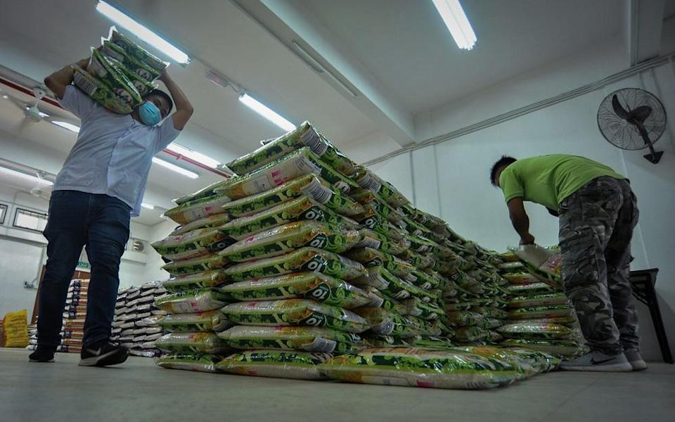 Staff at the Welfare Department in Labuan arrange bags of rice before distributing them to those affected by the Covid-19 pandemic, October 23, 2020. — Bernama pic