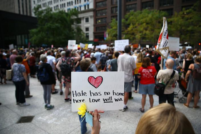 """A demonstrator holds a banner reading """"Hate Has No Home Here. Love Will Win"""" during an Aug. 13 protest at Federal Plaza Square in Chicago."""
