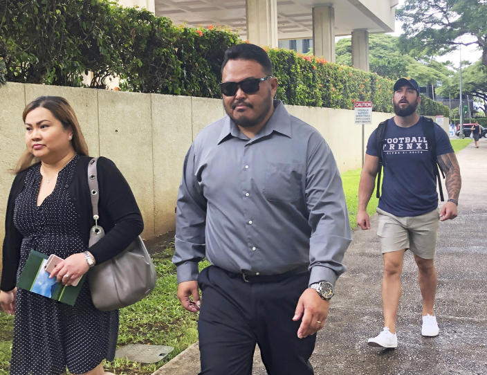 FILE - In this Sept. 25, 2019 file photo, former Honolulu police officer Reginald Ramones, center, walks down a street in Honolulu. Samuel Ingall, a homeless man, is suing the Honolulu Police Department and the city after he says officers forced him to lick a urinal in a public restroom. A U.S. judge sentenced a former Honolulu police officer Wednesday, July 15, 2020, to four years in prison, telling him to imagine someone doing that to his two young daughters. The homeless man was just as defenseless and powerless as John Rabago's 10- and 8-year-old daughters, U.S. District Judge Leslie Kobayashi said. (AP Photo/Jennifer Sinco Kelleher, File)