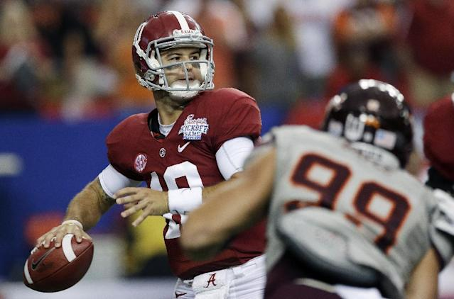 Alabama quarterback AJ McCarron (10) is pursued by Virginia Tech defensive end James Gayle (99) as he looks for a receiver in the first half of an NCAA college football game, Saturday, Aug. 31, 2013, in Atlanta. (AP Photo/Dave Martin)