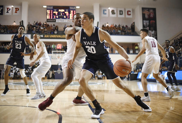 Yale's Paul Atkinson, front, dribbles as Harvard's Chris Lewis, back, defends during the first half of an NCAA college basketball game for the Ivy League championship at Yale University in New Haven, Conn., Sunday, March 17, 2019, in New Haven, Conn. (AP Photo/Jessica Hill)