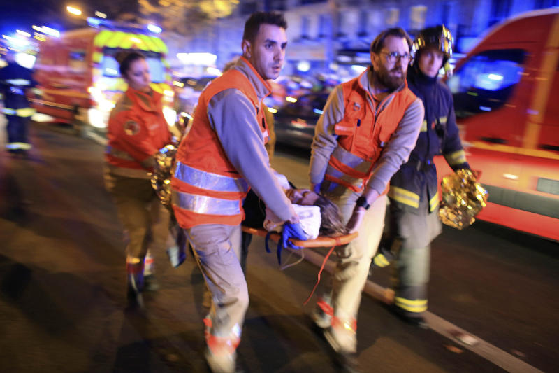 FILE - In this Nov. 13, 2015, file photo, a woman is being evacuated from the Bataclan concert hall after a shooting in Paris. France is commemorating the fourth anniversary of the Islamic State attacks in Paris. The attacks on Nov. 13, 2015, left 131 people dead at the country's national stadium, the Bataclan concert hall and bars and restaurants in the city center. (AP Photo/Thibault Camus, File)