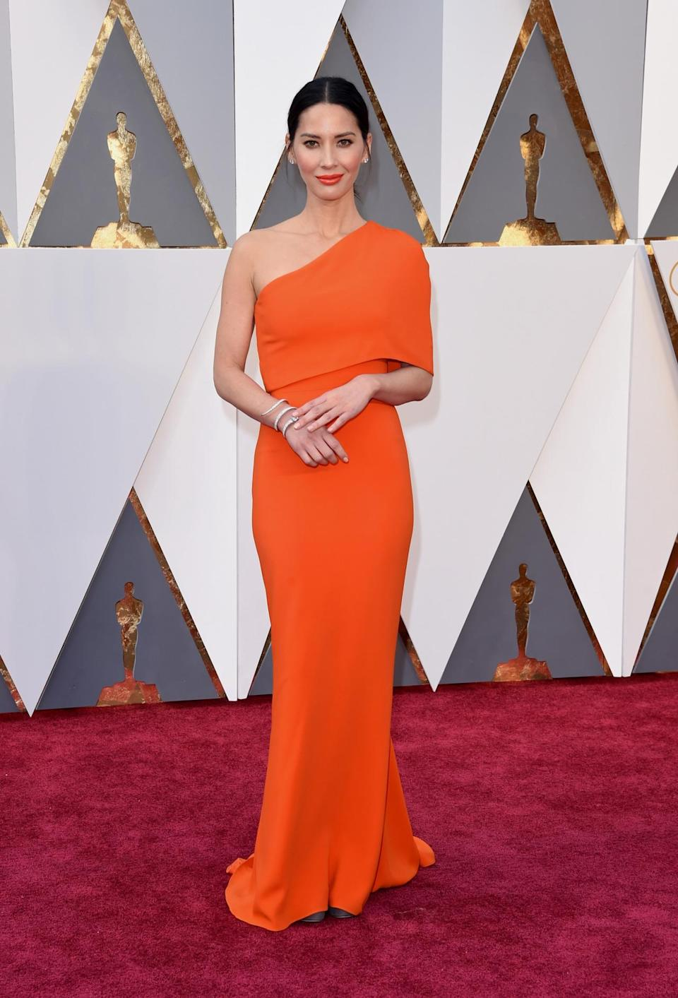 <p>Olivia Munn was matchy-matchy in an orange Stella McCartney one-shoulder gown and the same shade lip. <i><i>(Photo: Getty Images)</i></i></p>