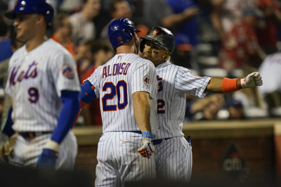 New York Mets' Francisco Lindor, right, celebrates with Pete Alonso, center, after hitting a grand slam during the sixth inning of a baseball game against the Pittsburgh Pirates Friday, July 9, 2021, in New York. (AP Photo/Frank Franklin II)