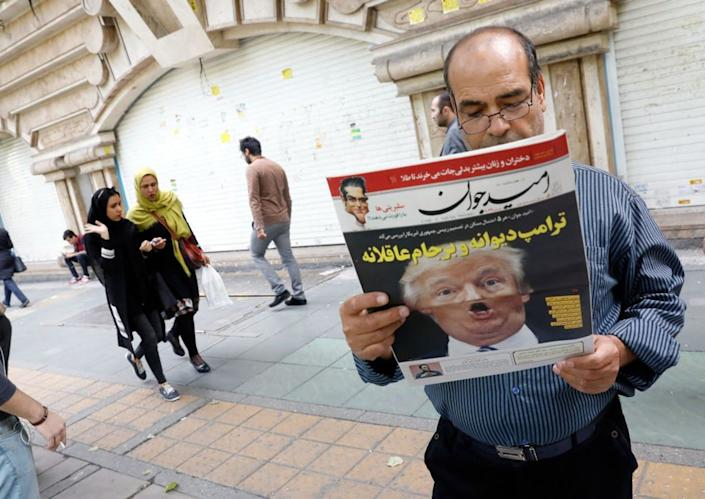 An Iranian man reads a copy of the daily newspaper 'Omid Javan' with a picture of Donald Trump on the cover.