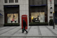 A person wearing a mask to curb the spread of coronavirus walks a traditional red phone box outside the Ralph Lauren fashion brand flagship store on New Oxford Street in London, during England's third coronavirus lockdown, Friday, March 26, 2021. The pandemic has battered the British economy, which has suffered its deepest recession in more than 300 years. Pubs, restaurants, theaters, hair salons and all stores selling nonessential items such as books and footwear have spent much of the past year closed. (AP Photo/Matt Dunham)