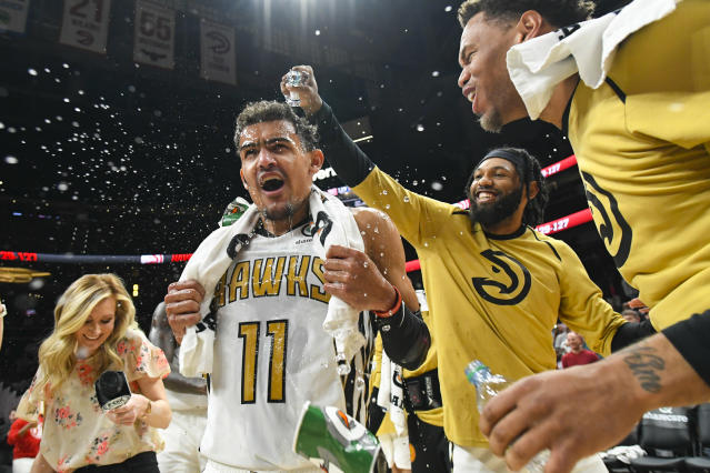 Atlanta Hawks guard Trae Young (11) is doused by forward DeAndre' Bembry as they and Justin Anderson, right, celebrate after Young's winning basket against the Philadelphia 76ers in an NBA basketball game Saturday, March 23, 2019, in Atlanta. (AP Photo/John Amis)