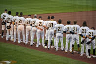 The Pittsburgh Pirates, all wearing Roberto Clemente's No. 21 for Roberto Clemente Day, watch a tribute to the Pirates Hall of Fame right fielder before the team's baseball game against the Chicago White Sox in Pittsburgh, Wednesday, Sept. 9, 2020. (AP Photo/Gene J. Puskar)