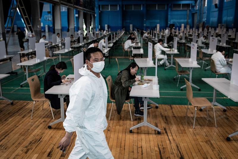 This photo taken on April 7, 2020 shows employees eating during lunch break at an auto plant of Dongfeng Honda in Wuhan in China's central Hubei province. - Thousands of relieved citizens streamed out of China's Wuhan on April 8 after authorities lifted months of lockdown at the coronavirus epicntre, offering some hope to the world despite record deaths in Europe and the United States. (Photo by STR / AFP) / China OUT (Photo by STR/AFP via Getty Images)