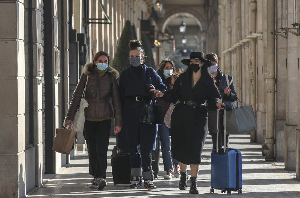 Women wearing face masks as a precaution against the coronavirus walks at the rue Rivoli in Paris, Friday, Nov. 6, 2020. The French government is supplying quick virus tests to nursing homes around the country, amid sharply rising numbers of virus infections and deaths in care homes in recent weeks. (AP Photos/Michel Euler)