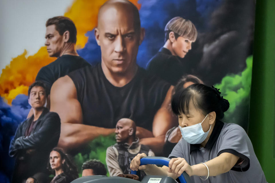 """A worker pushes cleaning equipment past a poster for the movie """"Fast & Furious 9"""" at a shopping mall in Beijing, Wednesday, May 26, 2021. Pro-wrestling champion and actor John Cena is apologizing after calling Taiwan a country in promotional interviews for his upcoming film """"Fast & Furious 9."""" (AP Photo/Mark Schiefelbein)"""