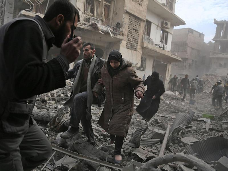 Civilians flee from an area hit by a reported regime air strike in Eastern Ghouta: AFP/Getty
