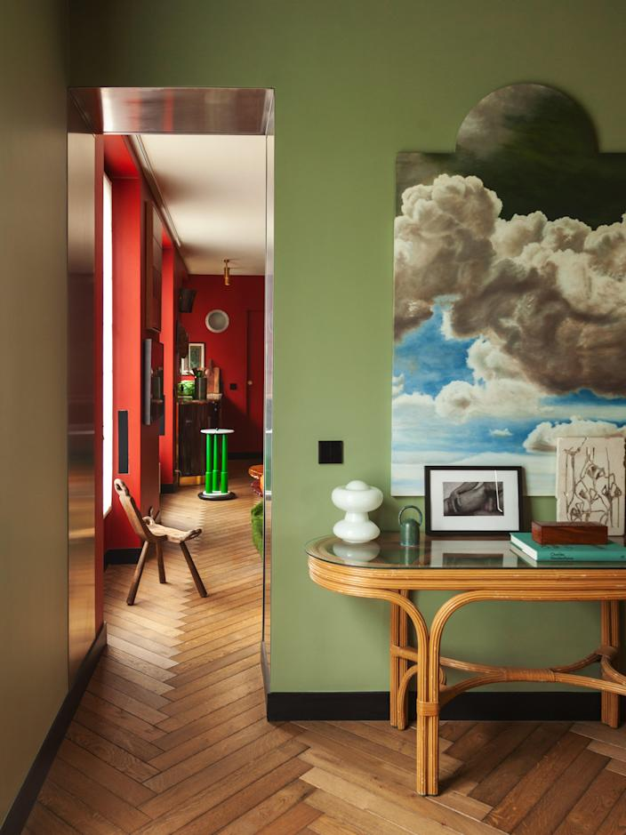 In the transition area between the living room and the bedroom, the clouds artwork is by Julien Gauthier and the white ceramic piece is by Nicolette Johnson. The table and lamp are vintage. On the left, the Spanish stool is from the 1930s.