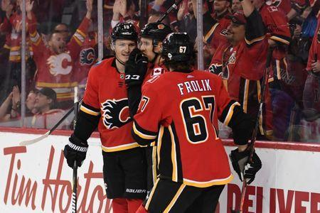 Mar 19, 2019; Calgary, Alberta, CAN; Calgary Flames left wing Matthew Tkachuk (19) celebrates with center Mikael Backlund (11) and right wing Michael Frolik (67) after scoring a empty net goal in the third period against the Columbus Blue Jackets at Scotiabank Saddledome. Flames won 4-2. Mandatory Credit: Candice Ward-USA TODAY Sports