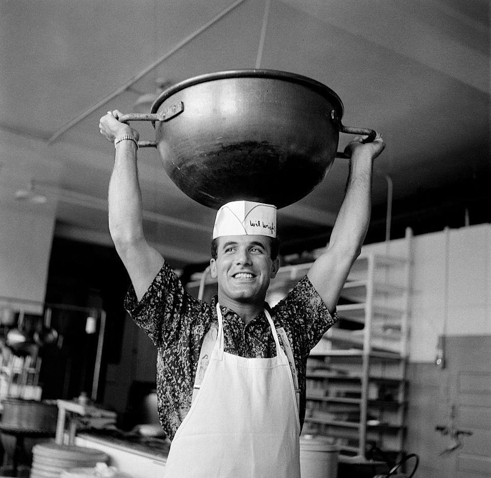 <p>Musician Dick Contino lifts a large kettle of chocolate over his head as he helps out at a Los Angeles ice cream parlor. </p>