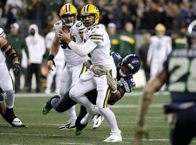 Green Bay Packers quarterback Aaron Rodgers, center, is sacked by Seattle Seahawks defensive end Rasheem Green during the second half of an NFL football game, Thursday, Nov. 15, 2018, in Seattle. (AP Photo/Elaine Thompson)