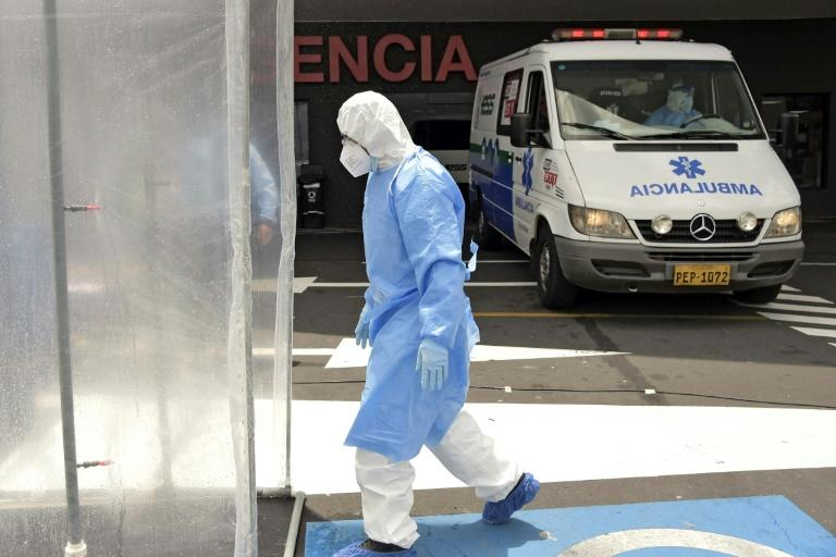 A paramedic enters the disinfection booth outside the emergency room of the IESS Sur Hospital in Quito on April 18, 2020 (AFP Photo/RODRIGO BUENDIA)
