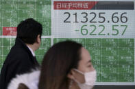 People walk past an electronic stock board showing Japan's Nikkei 225 index at a securities firm in Tokyo Friday, Feb. 28, 2020. Asian stock markets have fallen further on virus fears after Wall Street endured its biggest one-day drop in nine years. (AP Photo/Eugene Hoshiko)