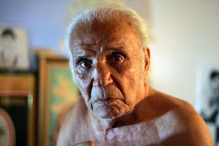 FILE PHOTO: Former middleweight boxing champion Jake LaMotta poses in New York October 28, 2009. LaMotta learned to fight with an ice pick in his hand in a Bronx schoolyard, battering all the way in later life to a world middleweight title in an era of 15-round fights. REUTERS/Teddy Blackburn/File Photo
