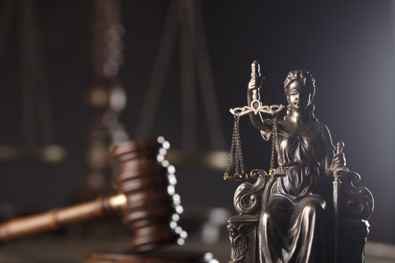 Themis, gavel and scale on wooden desk.