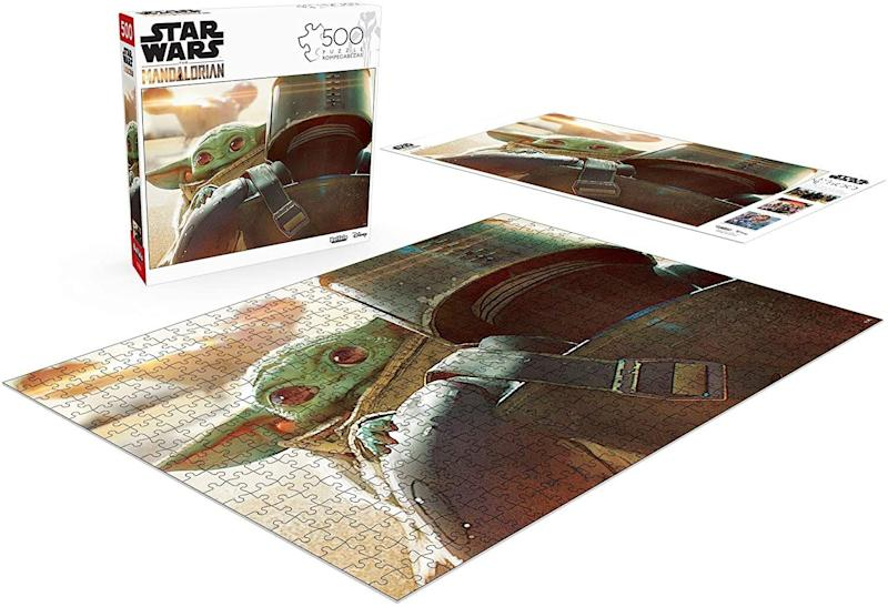 """If they're a fan of """"The Mandalorian,"""" they'll probably be a fan of <a href=""""https://amzn.to/2ZXsIr1"""" target=""""_blank"""" rel=""""noopener noreferrer"""">this jigsaw puzzle</a>featuringthe title character<i> and </i>Baby Yoda. <a href=""""https://amzn.to/2ZXsIr1"""" target=""""_blank"""" rel=""""noopener noreferrer"""">Find it for $10 at Amazon</a>."""