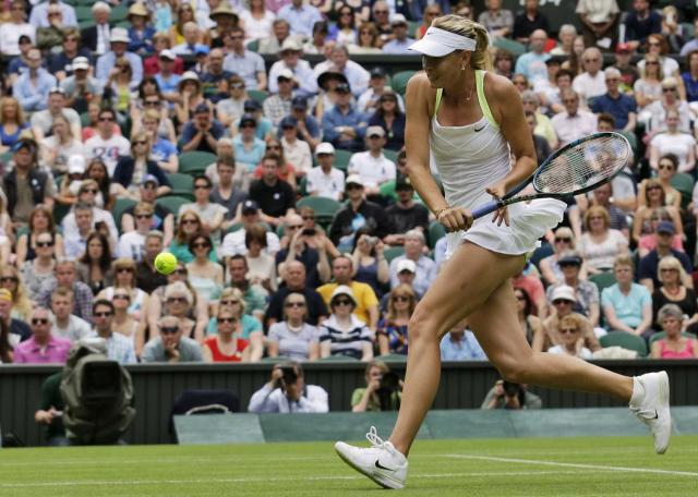 Maria Sharapova of Russia returns a shot to Anastasia Rodionova of Australia during a first round women's singles match at the All England Lawn Tennis Championships at Wimbledon, England, Monday, June 25, 2012. (AP Photo/Anja Niedringhaus)