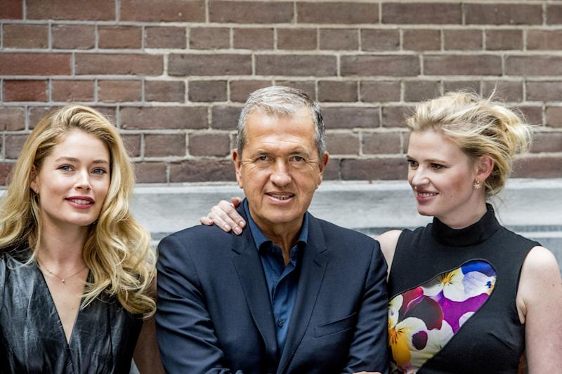 Peruvian photographer Mario Testino (C) poses with Dutch models Doutzen Kroes (L) and Lara Stone during the presentation of a special anniversary edition of Vogue Netherlands in Amsterdam on March 8, 2017. The issue's cover features a photo by Testino of the two models posing nude. / AFP PHOTO / ANP / Robin UTRECHT