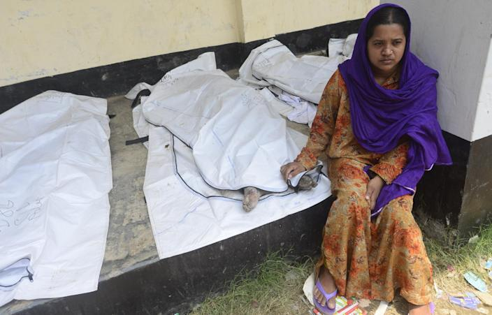 A Bangladeshi woman sits by a relative who died in a building collapse in Savar, near Dhaka, Bangladesh, Saturday, May 11, 2013. The death toll from Bangladesh's worst industrial disaster is more than 1,000 and climbing. More than 2,500 people were rescued in the immediate aftermath of the April 24 disaster. (AP Photo/Ismail Ferdous)