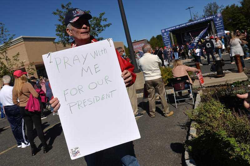 """A man holds a sign asking for people to pray with him for President Donald Trump who announced he tested COVID-19 the previous day, at a pro-Trump """"New York Triumph"""" rally, organised by the Staten Island Republican Party, held at Bricktown Center At Charleston in the New York City borough of Staten Island, NY."""
