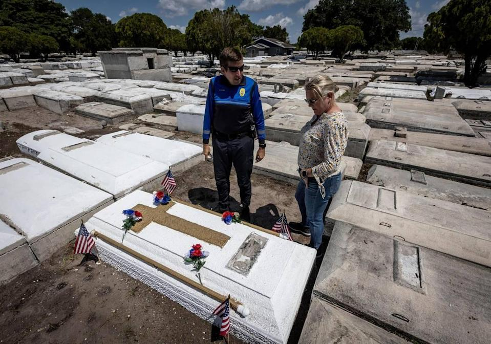 Miami, Florida, May 7 2021 - Commander Dan Kerr, left and retired Miami Detective Jerry Lynn Dellamico stand over what they believe to be Nathaniel Broom's grave at Lincoln Memorial Park in Allapatah. Kerr is currently looking into scanning the grave so they can confirm the identity of the remains inside
