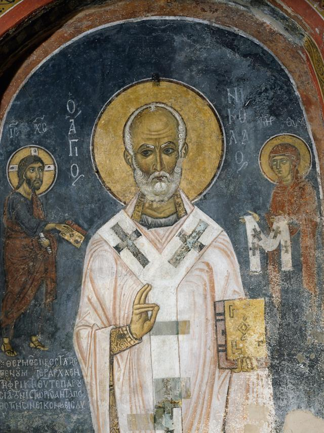 St. Nicholas of Myra is seen in this 12th-century fresco. The saint's acts of generosity, particularly to children, inspired the red and white-suitedfigureknown as Santa Claus.