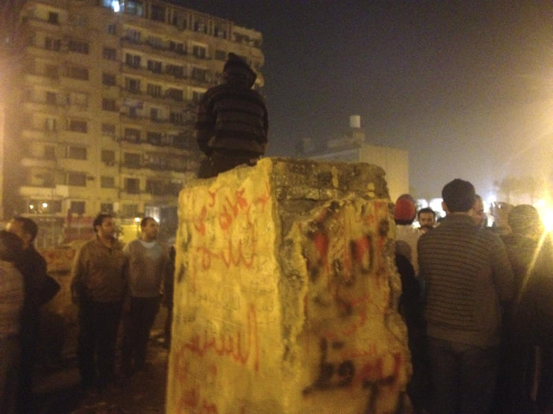 People gather around the foundation for the future memorial to Egyptian protesters killed in the country's uprising and more than two-and-a-half years of turmoil after it was damaged in Cairo's famed Tahrir Square, Tuesday, Nov. 19, 2013. Unknown assailants attacked, chipped away and sprayed graffiti on the huge stone early on Tuesday, just hours after it was inaugurated by the country's interim prime minister. (AP Photo/Sarah El Deeb)