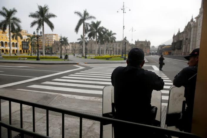 Police officers guard an empty Plaza de Armas after Peru's government deployed military personnel to block major roads, as the country rolled out a 15-day state of emergency to slow the spread of coronavirus disease (COVID-19), in Lima