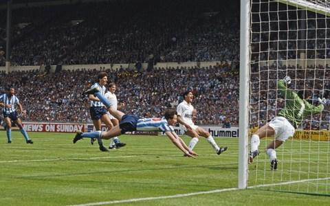 """Even now, nearly 31 years on from that scorching Wembley afternoon, Steve Ogrizovic cannot escape Coventry City's famous day in the sun. """"Wherever I go, there will be somebody mentioning the 1987 FA Cup final against Spurs,"""" he says, smiling. """"People will say it was the best day of their lives. I always ask them 'what about the day you got married, or the day when your kids were born' but they just want to talk about the final. The fans who went to Wembley have dined out on it ever since. Not a day goes by without it being mentioned. """"If you talk to the staff here, they'll also say I mention it every day – but I can assure you it's not true…"""" With Ogrizovic in goal, Coventry secured one of the most memorable victories in the cup's long history when they defeated Tottenham Hotspur 3-2. Spurs - runaway favourites, despite only finishing eight points ahead of Coventry in the First Division that season - led twice but City, playing in their first major final, were in no mood to lie down. Coventry striker Keith Houchen dives to head past Spurs goalkeeper Ray Clemence - as Chris Hughton, now Brighton manager, watches on Credit: Hulton Archive After Keith Houchen's spectacular airborne header took the game into extra time, the defining moment came in the 95th minute, when the unfortunate Gary Mabbutt diverted Lloyd McGrath's cross over his own goalkeeper Ray Clemence for the winner. The moment was immortalised by the creation of Coventry's famous fanzine 'Gary Mabbutt's Knee', while the BBC's John Motson described the game as """"the finest final I've had the pleasure of commentating on"""". For Ogrizovic, now Coventry's goalkeeping coach, the memories remain vivid. """"It was the game which really put Coventry on the map, in terms of being the first major trophy the club had ever won,"""" he recalls. """"The great thing about that game is not only Coventry winning but how it's remembered as an entertaining, exciting final. """"The finals weren't always that entertaining in those days, whic"""