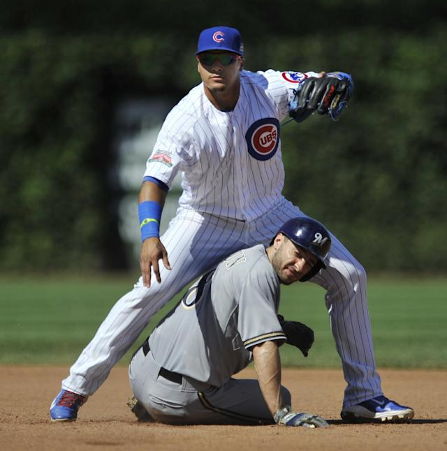Chicago Cubs second baseman Javier Baez top, watches his throw to first base after forcing out Milwaukee Brewers' Ryan Braun (8), at second base during the fourth inning of a baseball game in Chicago, Monday, Sept. 1, 2014. (AP Photo/Paul Beaty)