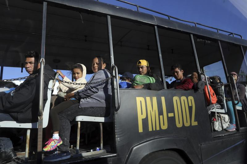 Members of a Central American migrant caravan hoping to reach the U.S. border travel in a police bus in Guadalajara, Mexico, Tuesday, Nov. 13, 2018. The thousands of Central American migrants left shelters in Guadalajara early Tuesday and were taken by bus to a highway tollbooth to wait for rides to their next destination, however, no other buses showed up and few trucks passed to pick them up, leaving many to walk. (AP Photo/Rodrigo Abd)