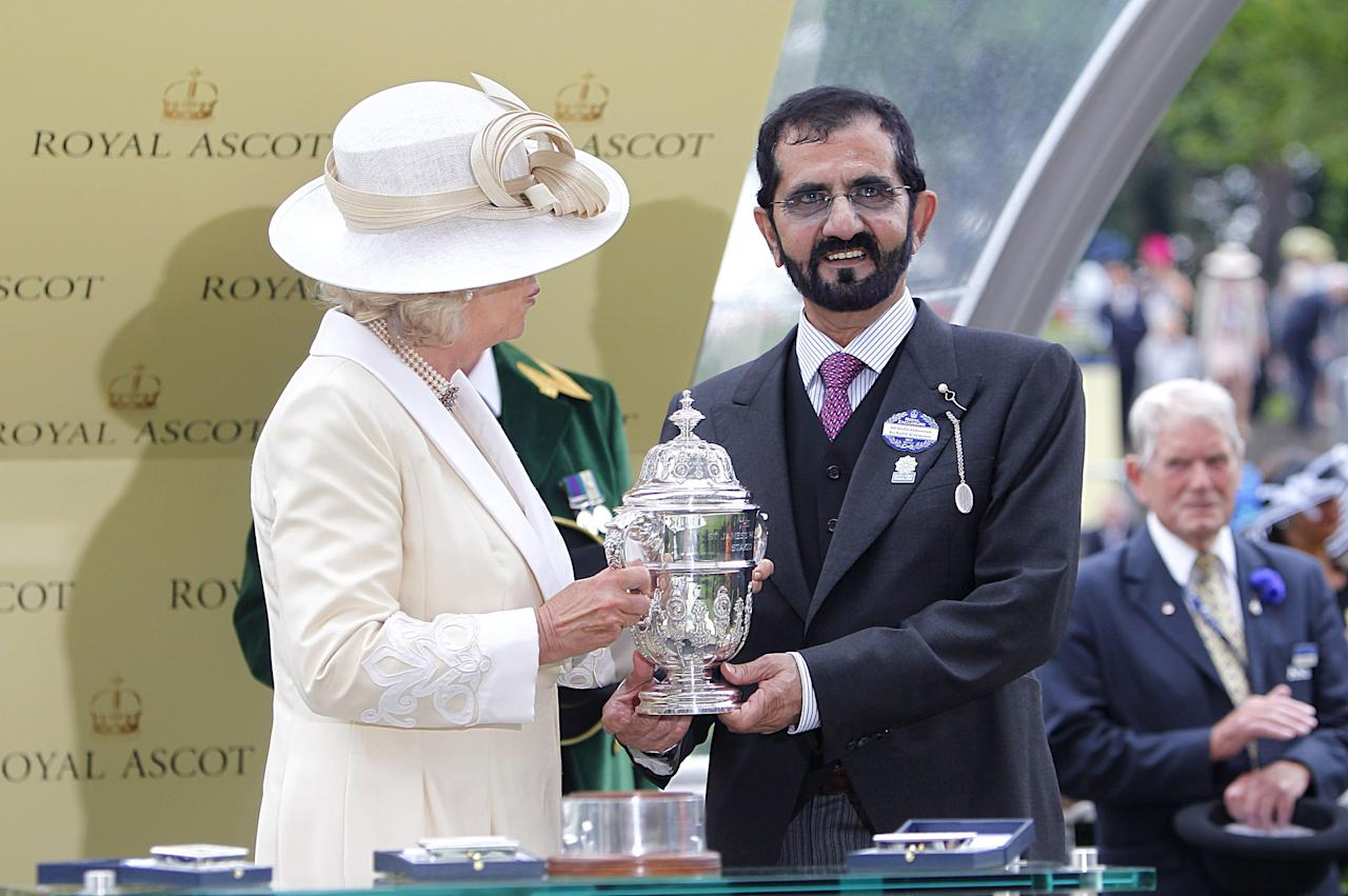 Mohammed bin Rashid Al Maktoum is presented with a trophy by The Duchess of Cornwall after his horse Dawn Approach won The St James's Palace Stakes