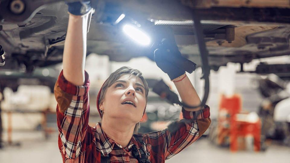 Female technician working with a flashlight under a lifted car.
