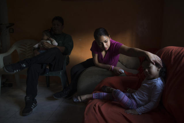 <p>Jimmy Chasi Sanguna holds his 1-year-old daughter, Daniela, while his wife Liseth Saavedra, 22 years old, caresses her 3-yea- old daughter, Dayana, as they wait for a judicial commission and the police to evict them, Madrid, April 11, 2014. (AP Photo/Andres Kudacki) </p>