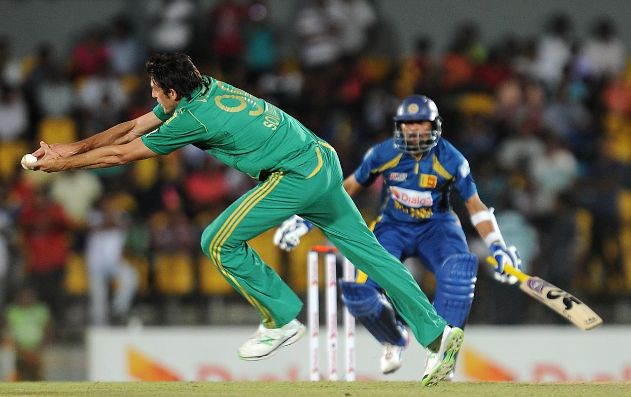 South African cricketer David Wiese (L) dives as he attempts to field a ball hit by Sri Lankan batsman Tillakaratne Dilshan (R) during the third and final Twenty20 cricket match between Sri Lanka and South Africa at the Suriyawewa Mahinda Rajapakse International Cricket Stadium in the southern district of Hambantota on August 6, 2013. AFP PHOTO/ LAKRUWAN WANNIARACHCHI